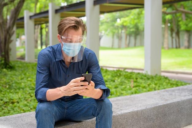 Jonge man met behulp van telefoon met masker en gezichtsscherm zittend in het park