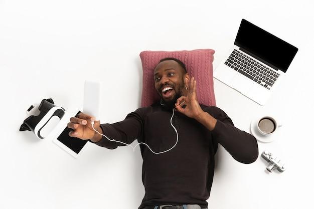 Jonge man met behulp van telefoon omringd door gadgets geïsoleerd