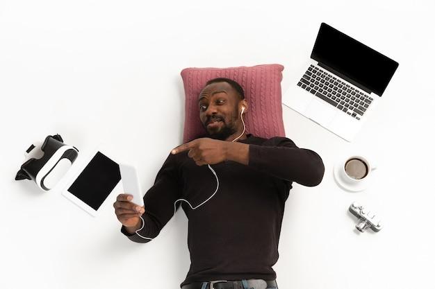Jonge man met behulp van telefoon omringd door gadgets