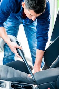 Jonge man met behulp van vacuüm voor het reinigen van het interieur van een auto