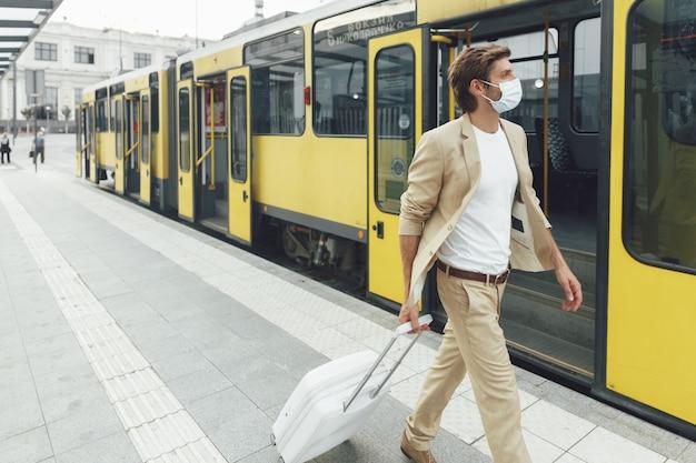 Jonge man met beschermend medisch masker tijdens het lopen op station met witte koffer