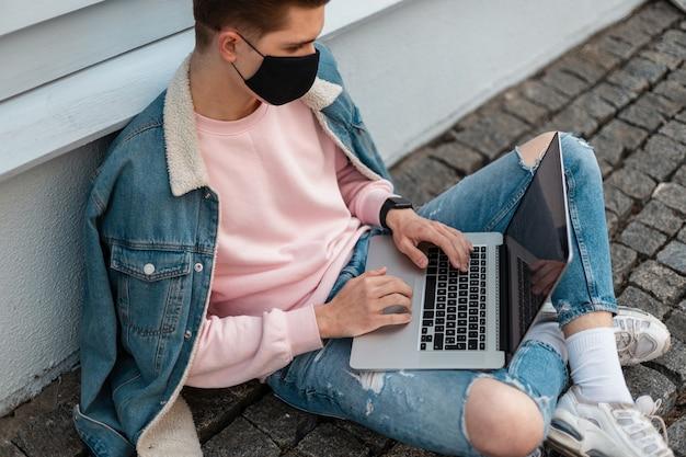 Jonge man met beschermend zwart masker in modieuze casual denim kleding met laptop zit op straat in de buurt van muur. guy werkt op afstand op internet aan een nieuw creatief project dat zichzelf beschermt tegen een pandemie.