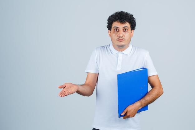Jonge man met bestandsmap en hand uitstrekkend naar camera in wit t-shirt en spijkerbroek en perplex kijkend. vooraanzicht.