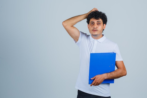 Jonge man met bestandsmap, hand op het hoofd in wit t-shirt en spijkerbroek en peinzend kijkend. vooraanzicht.