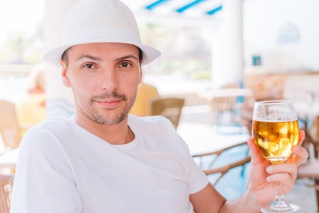 Jonge man met bier op het strand in openlucht bar