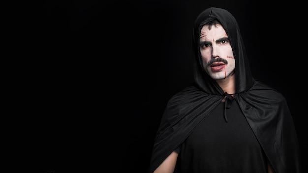 Jonge man met bleke gezicht en littekens poseren in halloween-kostuum