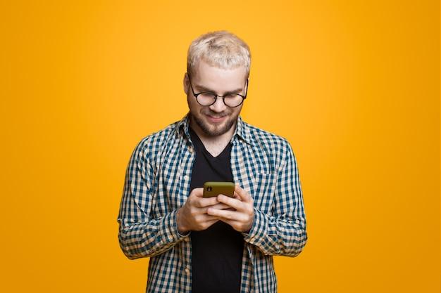 Jonge man met blond haar en baard met behulp van een telefoon is aan het chatten op een gele muur