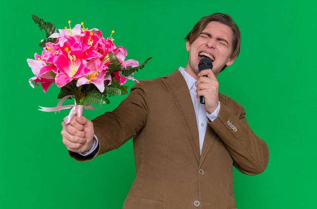 Jonge man met boeket bloemen en microfoon blij en opgewonden