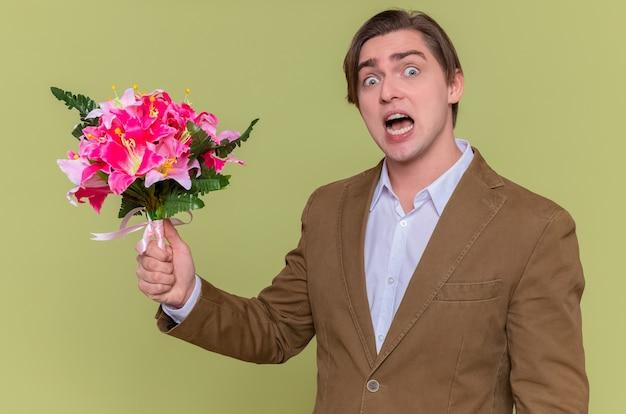 Jonge man met boeket bloemen kijken camera geïrriteerd
