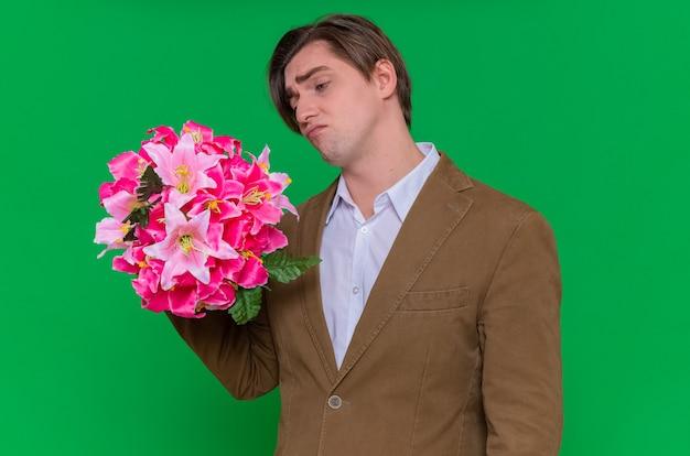 Jonge man met boeket bloemen kijken met droevige uitdrukking gaan feliciteren met internationale vrouwendag maart concept