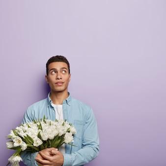 Jonge man met boeket van witte bloemen