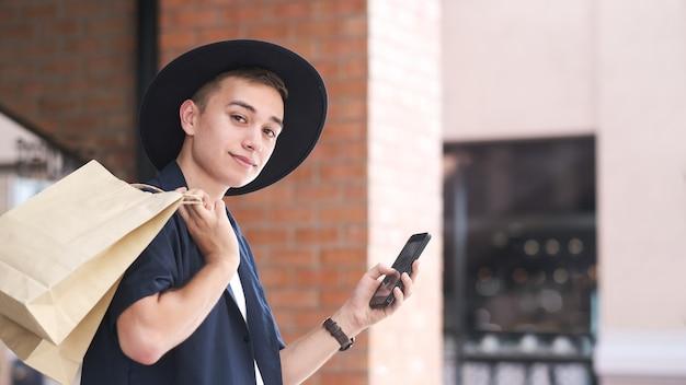 Jonge man met boodschappentassen gebruikt een mobiele telefoon tijdens het winkelen