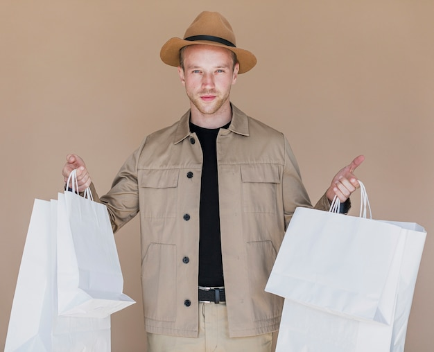 Jonge man met boodschappentassen in beide handen