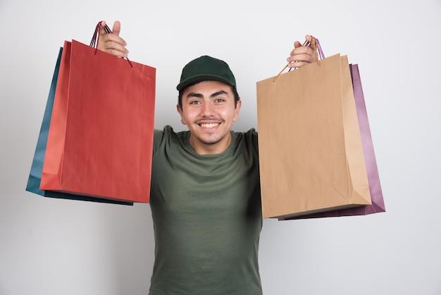 Jonge man met boodschappentassen op witte achtergrond.