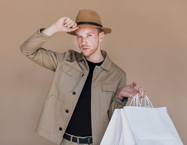 Jonge man met boodschappentassen op zoek naar de camera