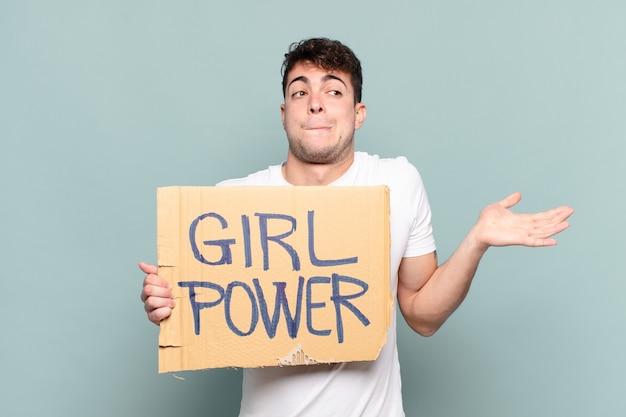 Jonge man met bordje met tekst: girl power. feminisme concept
