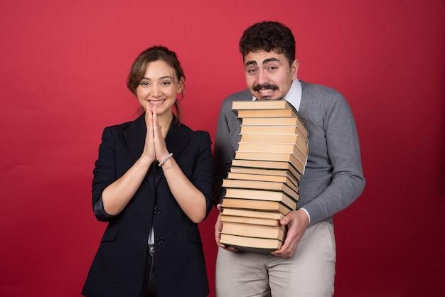 Jonge man met bosboeken en vrouwencollega die gelukkig glimlachen