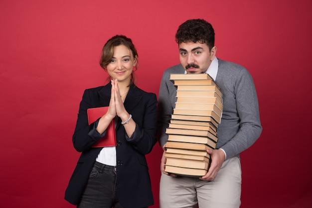 Jonge man met bosboeken en vrouwencollega die voor camera stellen