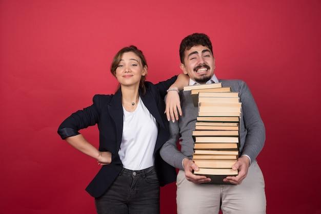 Jonge man met bosboeken en vrouwencollega die zich op rode muur bevindt