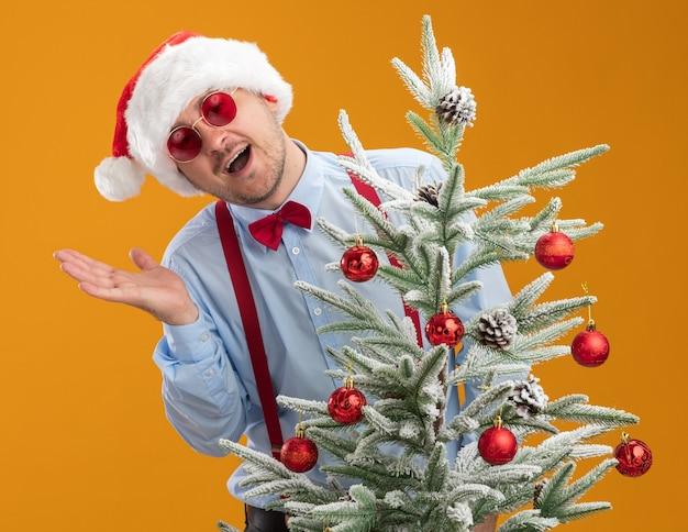 Jonge man met bretels strikje in kerstmuts en rode bril kijken camera blij en verrast in goed humeur staande in de buurt van kerstboom over oranje achtergrond