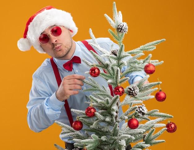Jonge man met bretels strikje in kerstmuts en rode bril permanent achter kerstboom blij en verbaasd opknoping speelgoed op boom over oranje achtergrond