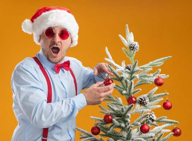 Jonge man met bretels strikje in kerstmuts en rode bril permanent in de buurt van kerstboom opknoping speelgoed op boom blij en verrast over oranje achtergrond