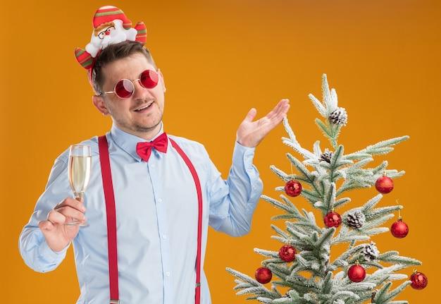 Jonge man met bretels strikje in rand met kerstman en rode bril permanent naast kerstboom met glas champagne blij en vrolijk op oranje achtergrond