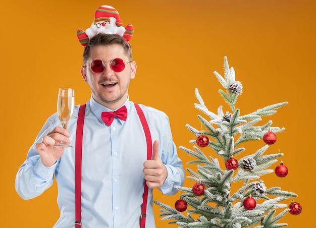 Jonge man met bretels strikje in rand met kerstman en rode bril permanent naast kerstboom met glas champagne duimen opdagen blij en vrolijk op oranje achtergrond