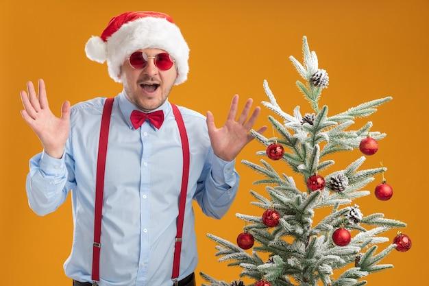 Jonge man met bretels vlinderdas in kerstmuts en rode bril blij en verrast met opgeheven armen staande in de buurt van kerstboom over oranje muur