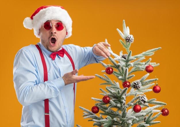 Jonge man met bretels vlinderdas in kerstmuts en rode bril permanent in de buurt van de kerstboom blij en verbaasd opknoping speelgoed op boom over oranje muur