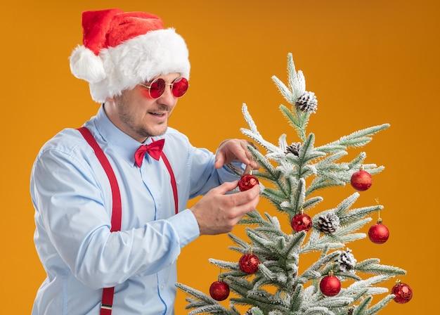 Jonge man met bretels vlinderdas in kerstmuts en rode bril staande in de buurt van kerstboom opknoping speelgoed op de boom blij en boos over oranje muur