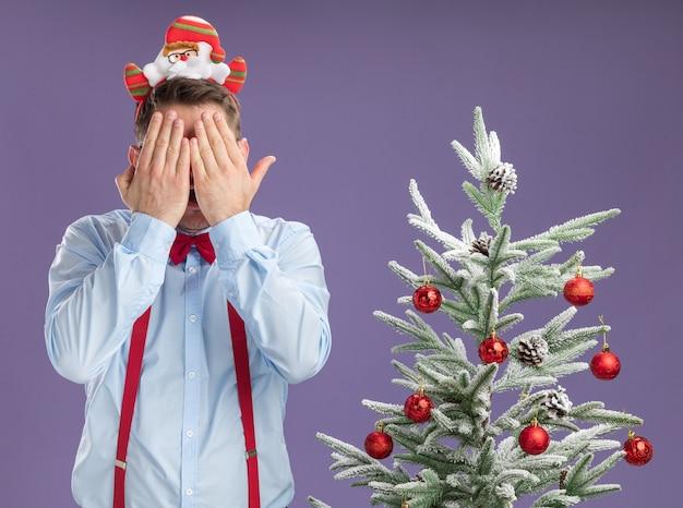 Jonge man met bretels vlinderdas in rand met kerstman en rode bril staan naast kerstboom die betrekking hebben op gezicht met handen over paarse achtergrond