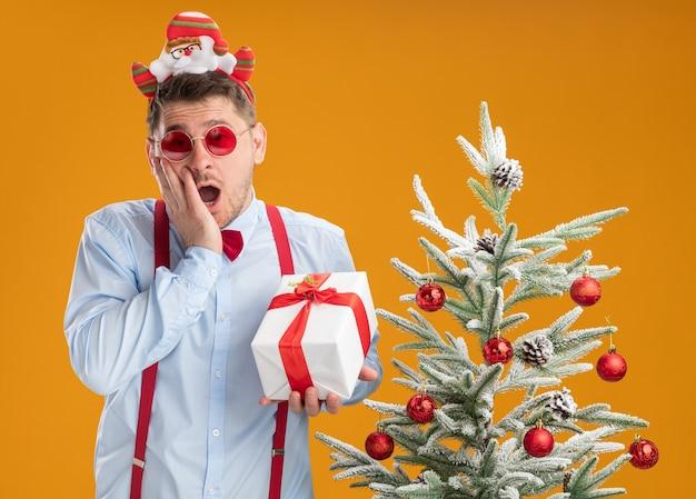 Jonge man met bretels vlinderdas in rand met kerstman en rode bril staande naast de kerstboom met een cadeau blij en opgewonden over oranje achtergrond