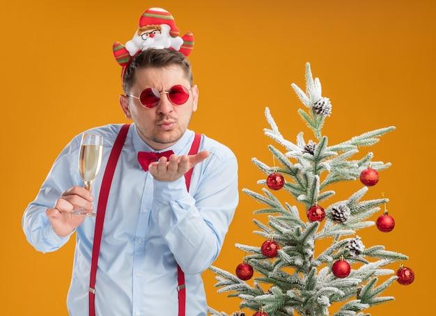 Jonge man met bretels vlinderdas in rand met kerstman en rode bril staande naast kerstboom met glas champagne blij en vrolijk blaast een kus over oranje achtergrond