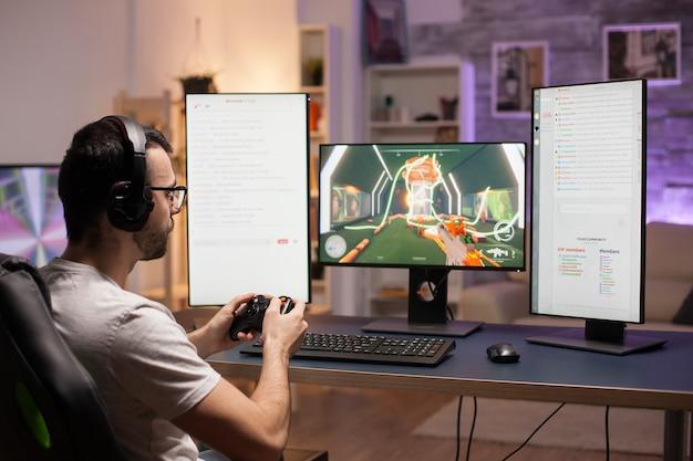 Jonge man met bril die thuis schietspellen speelt met behulp van een draadloze controller.