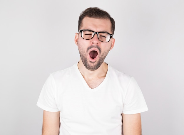 Jonge man met bril gaapt van vermoeidheid tegen witte achtergrond.