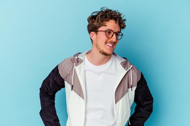 Jonge man met bril geïsoleerd op blauwe muur zelfverzekerd handen op de heupen te houden