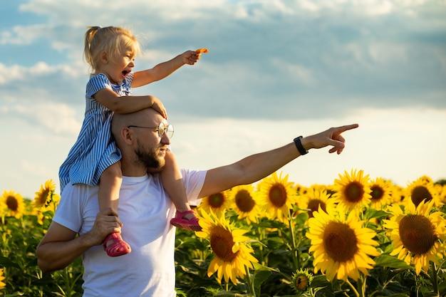Jonge man met bril houdt een kind op zijn schouders en wijst met zijn hand naar iets op een zonnebloemveld.