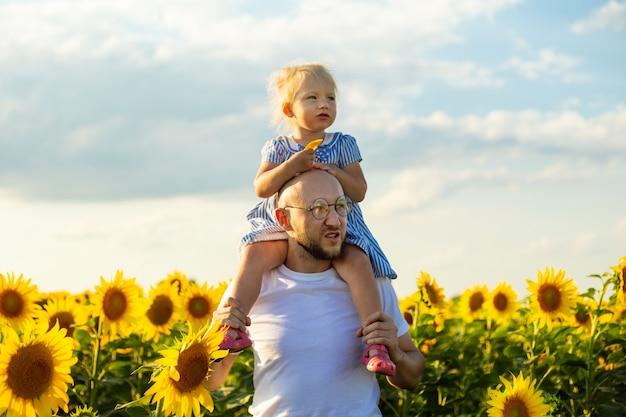 Jonge man met bril houdt een kind op zijn schouders op een zonnebloem veld.