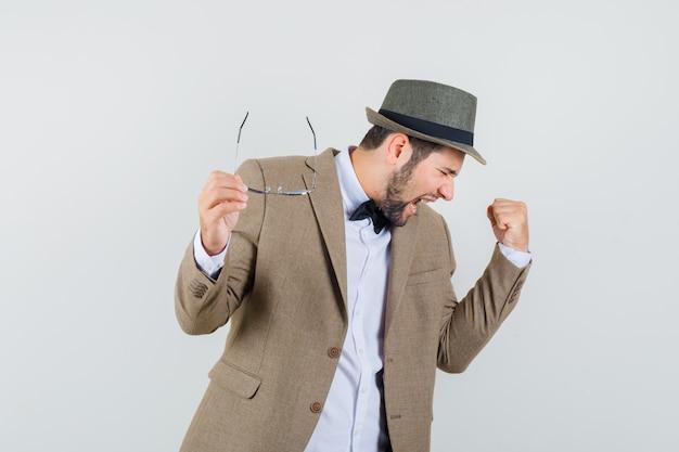 Jonge man met bril met winnaar gebaar in pak, hoed en op zoek gelukt, vooraanzicht.