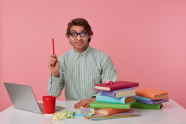 Jonge man met bril zit aan de tafel en werkt met laptop, kijkt naar de camera, houdt een potlood in de hand, heeft een cool idee, geïsoleerd op roze achtergrond.