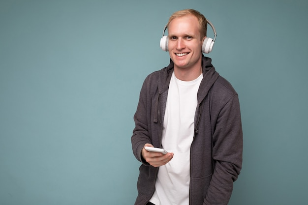 Jonge man met casual witte t-shirt geïsoleerd op blauwe achtergrond