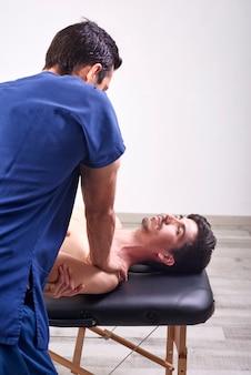 Jonge man met chiropractie schouder aanpassing.