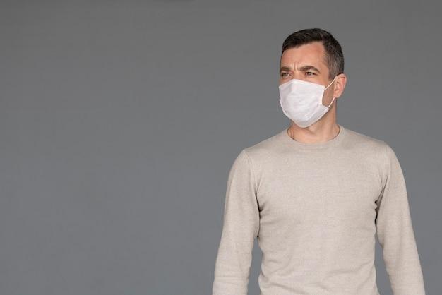 Jonge man met chirurgisch wit gezichtsmasker en zwarte handschoenen geïsoleerd op een grijze achtergrond met kopie ruimte