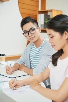 Jonge man met coworking vrouw in kantoor