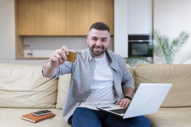 Jonge man met creditcard en het gebruik van telefoon thuis kantoor