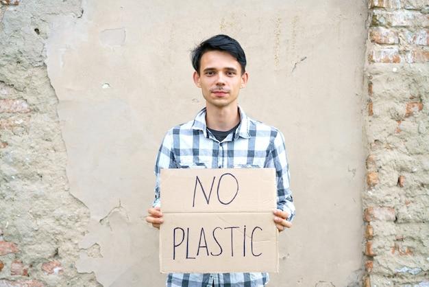Jonge man met de inscriptie op het karton geen plastic blanke man bij een demonstratie tegen ...