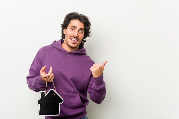 Jonge man met de vorm van een huispictogram wijst met duimvinger weg, lachend en zorgeloos.