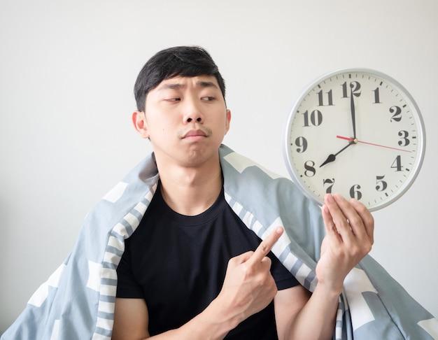 Jonge man met deken bedekt zijn lichaam en kijkt met de vinger naar de klok in de hand, voelt zich verveeld in het gezicht