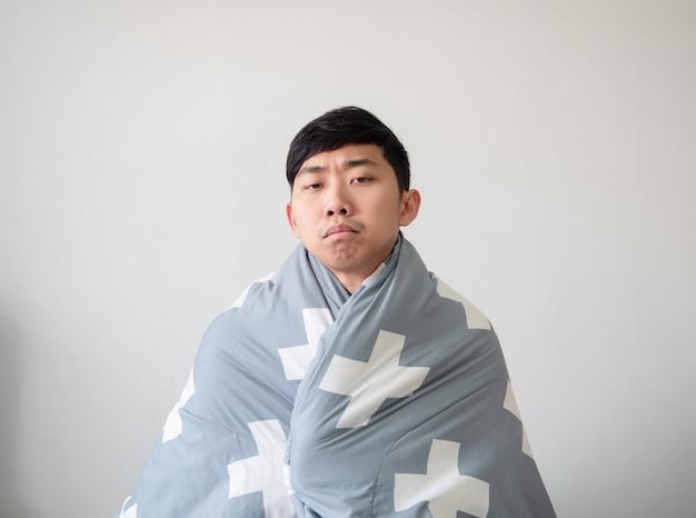 Jonge man met deken bedekt zijn lichaam en voelt zich verveeld in het gezicht, kijk naar de camera op wit geïsoleerd